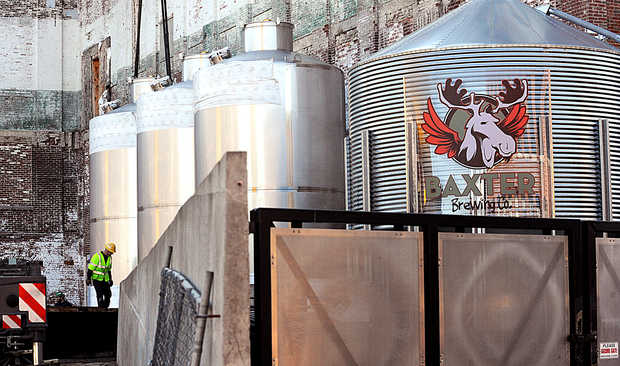 "An employee of Cote Crane and Rigging works to level one of Baxter Brewing's three new 8,000-gallon fermentation tanks during delivery and installation Monday in Lewiston. The tanks will double the craft brewer's production according to Luke Livingston, the president and founder of Baxter Brewing. The company hopes to add three identical tanks over the next three years. ""Most of this beer will be for Maine,"" said Chelsea Livingston, business manager at Baxter Brewing. ""Especially going into the summer months with the beaches and seasonal accounts."" Each tank will produce more than 85,000 cans of beer."