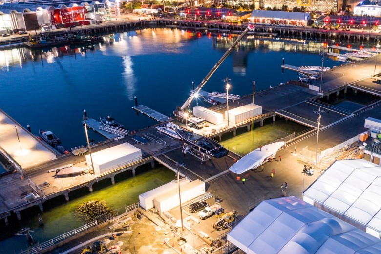 PATRIOT arrives at the American Magic team base in Auckland's Wynyard Quarter. DEFIANT rests uncovered to PATRIOT's left. The Emirates Team New Zealand  base is visible at the top left. © American Magic / Will Ricketson
