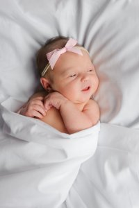 Newborn baby in white sheet with pink bow in hair