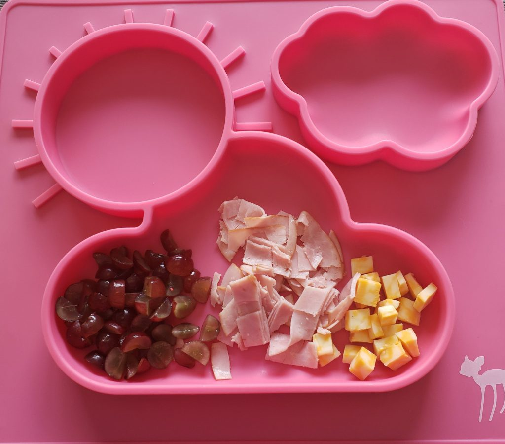 Pink kids divided plate filled with cubed cheese, ham, and grapes