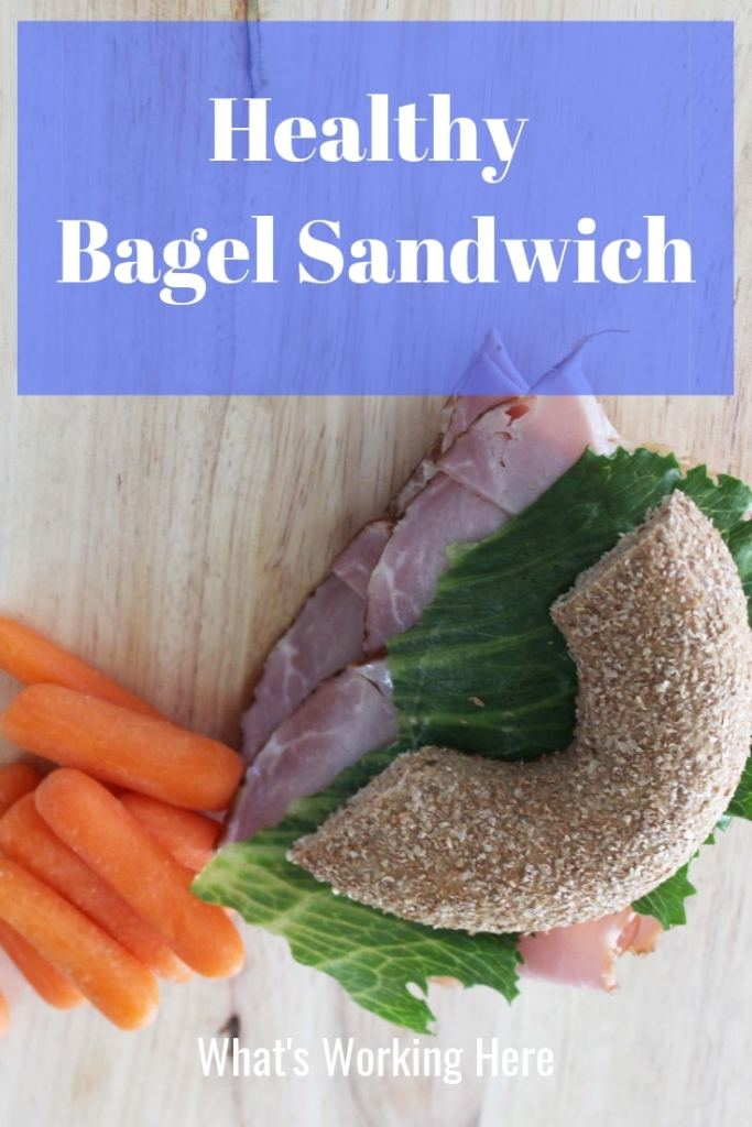 Healthy Bagel Sandwich - ham and cheese sandwich with lettuce on a whole wheat bagel with a side of baby carrots