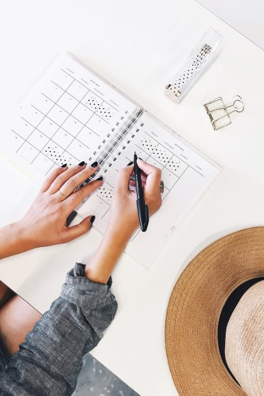 woman writing in organizer