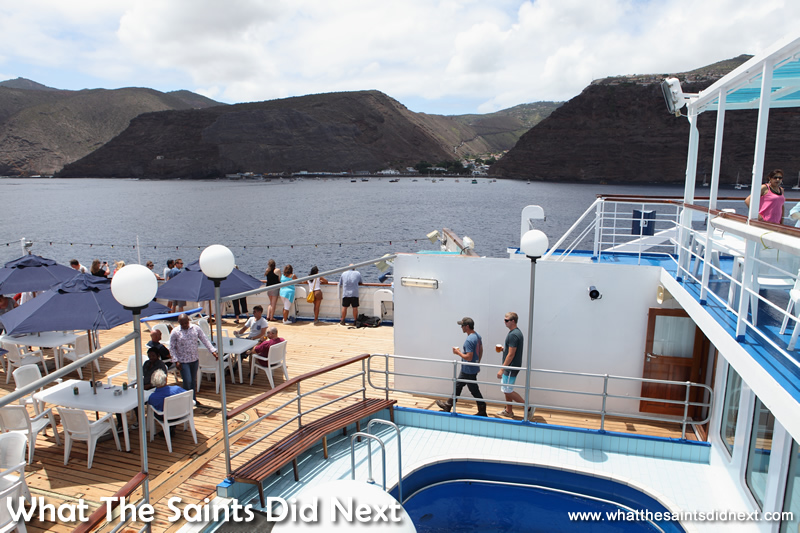 Passengers gather on the Sun Deck to watch the departure from James Bay. Voyage on the RMS St Helena.