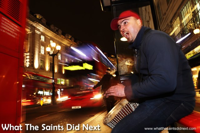 The city sparkles as a backdrop for Dan's performance.  Homeless Bucket Drum Busker Living On The Streets Of London.
