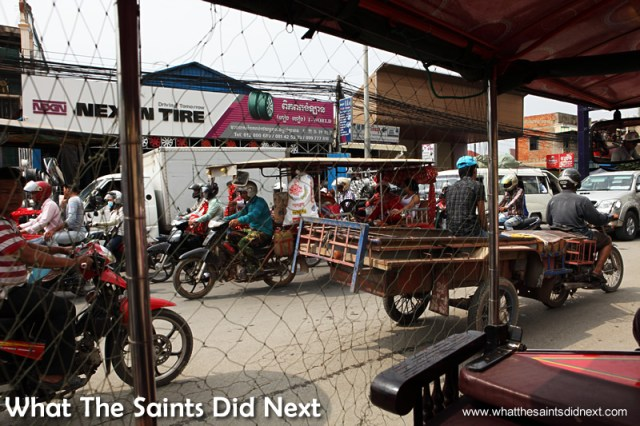 The bedlam of the Phnom Penh traffic viewed up close from inside a tuk tuk. Watching Cambodia Traffic.