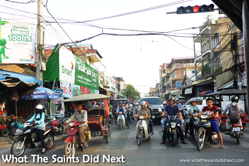 Not all intersections have traffic lights, but this one does which halts everyone for a minute. Watching Cambodia Traffic.