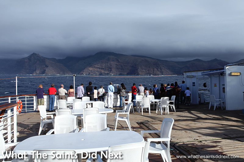 All change soon! Passengers on the RMS St Helena arriving from Cape Town and getting their first look at the island as the ship approaches.