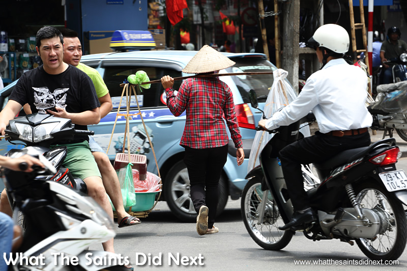 Local street sellers show no fear and just stroll right through the traffic.  Crossing The Street In Hanoi Vietnam.