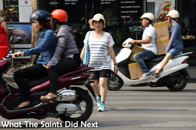 This lady just looks straight ahead and goes for it.  Crossing The Street In Hanoi Vietnam.