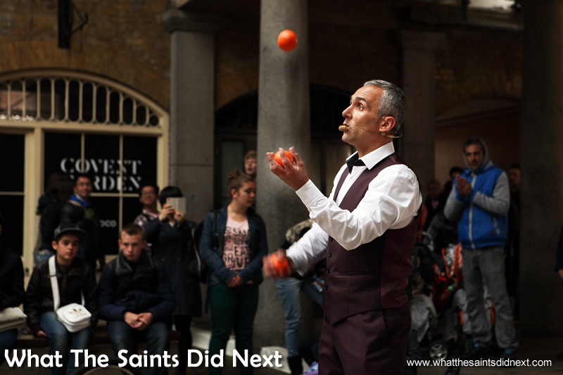 A street entertainer performing in Covent Garden, London. This covered market is a popular destination for tourists.