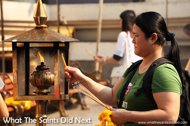 Candles being lit at the Erawan Shrine.