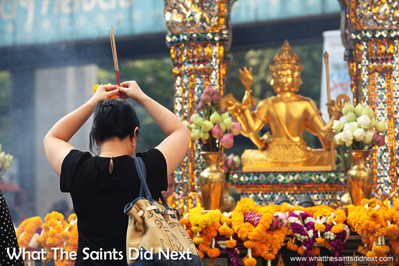 A worshipper at the Erawan Shrine in Bangkok, Thailand, burning incense before the gold statue of the Buddah, Phra Phrom.