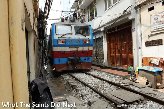 A Tight Squeeze! The Hanoi to Ho Chi Minh City train filling the gap. Train track running through the narrow Train Street in Hanoi.