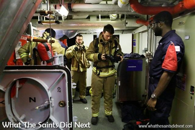 Crew members suiting up for an emergency fire drill onboard HMS Lancaster.