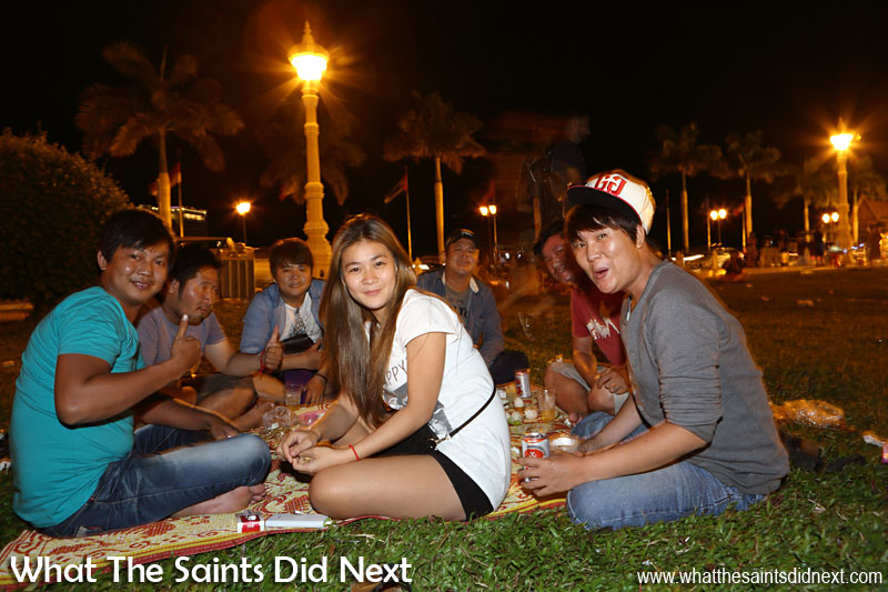 Group of young friends in the park by the Riverfront, out for the night along with hundreds of other people.