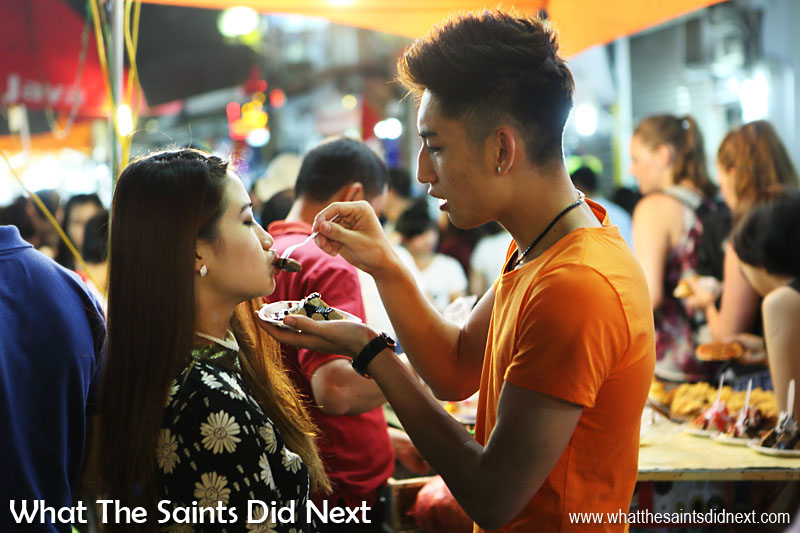 A tender moment in Hanoi's night street market, on Hàng Đào street in Vietnam. Night markets are very popular in Southeast Asia and a great place to observe culture and capture spontaneous moments like this. For the full story and pictures of Hanoi's night street market, Click Here.