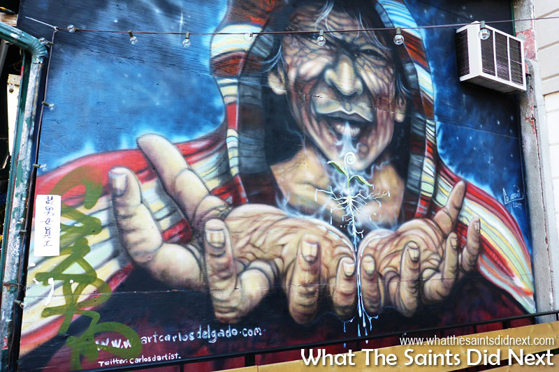 Attraction to this mural was powerful with the beckoning hands and aged lines of the wise face. Note the twitter account of the artist. Graffiti murals of Kensington Market in Toronto.