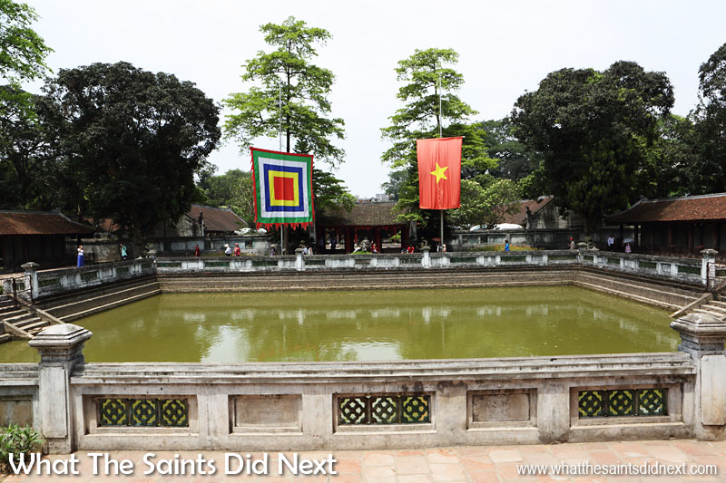 The distinctive Vietnamese flag and the festival flag of the Five Elements flutters over the Well of Heavenly Clarity. To the left and right are the rows of stelae of doctors.