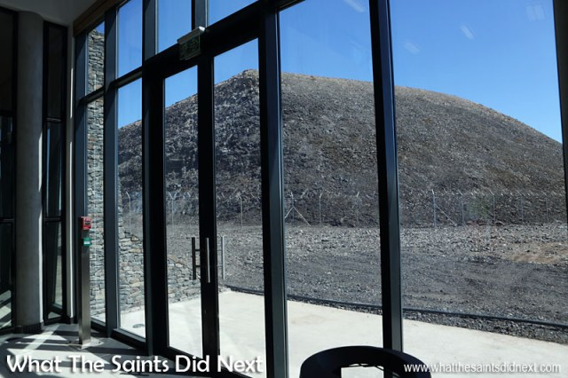 The view from inside the Baggage Reclaim hall of the stone hillside outside. The dry stone cladding on the terminal building can also be seen to the left.