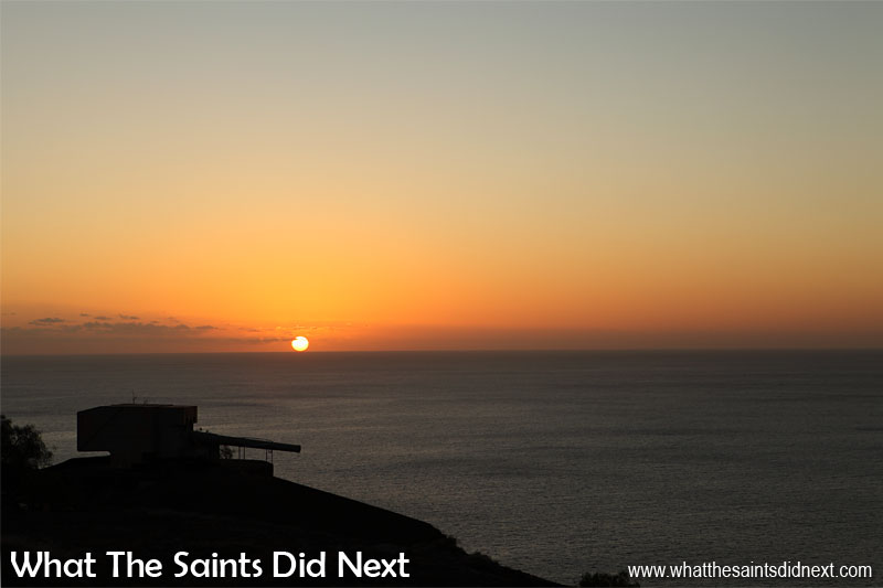 16 Pictures Celebrating St Helena Day 2016. Sunsets from the Half Tree Hollow area are normally quite spectacular on St Helena. Here the dark Atlantic Ocean calmly retrieves the sun from another day, watched over by one of the guns at Ladder Hill.
