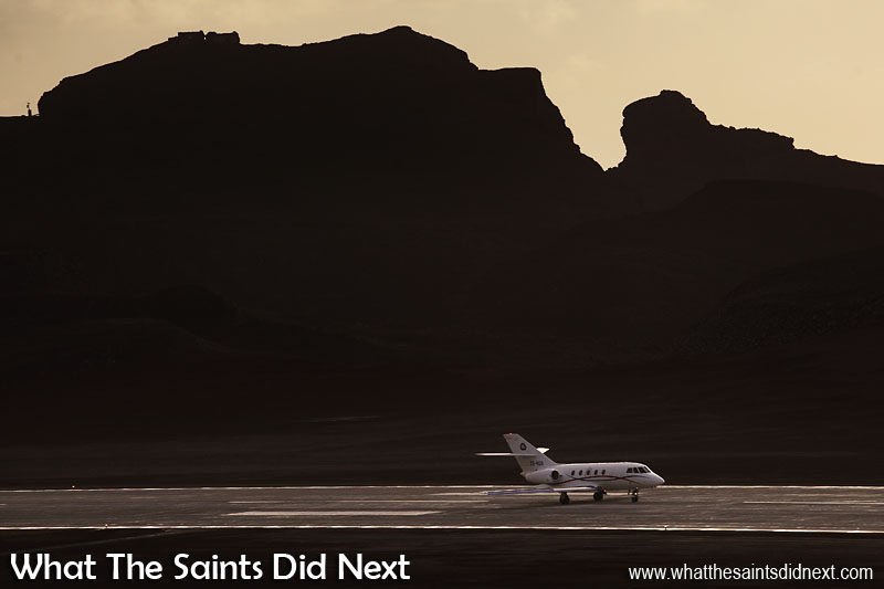 07:34. Beneath the bulk of King & Queen Rock and Prosperous Bay House on St Helena, the Guardian Air, Falcon 20, accelerates along the runway during take off.