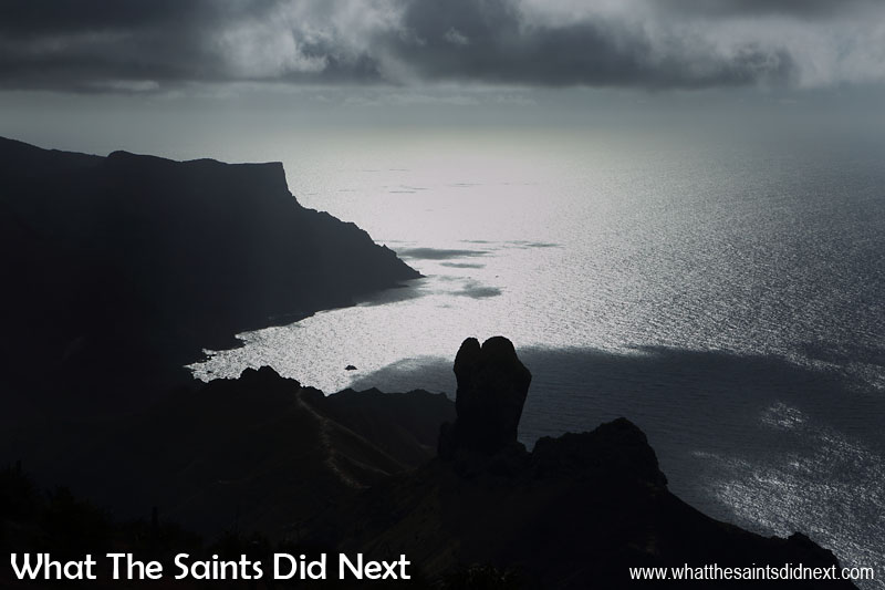 On an early morning hike to Blue Point, the sun turns the Sandy Bay landscape into a silhouette. The square cornered cliff top in the distance is Sandy Bay Barn, another post box walk. The knobbly top of Lot's Wife column pokes up in the foreground. Blue Point post box walk, St Helena Island.