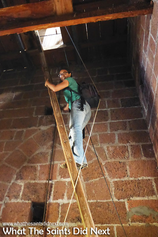 This is what is known as a 'secure grip.' Climbing the ladder up through the bell tower to reach the clock at the top. St James Church clock tower, Jamestown, St Helena.
