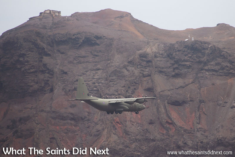 The low profile camouflage paint job almost hides the RAF C-130J Hercules against the King and Queen headland, topped by Prosperous Bay Plain House. RAF, C130 Hercules at St Helena Airport.