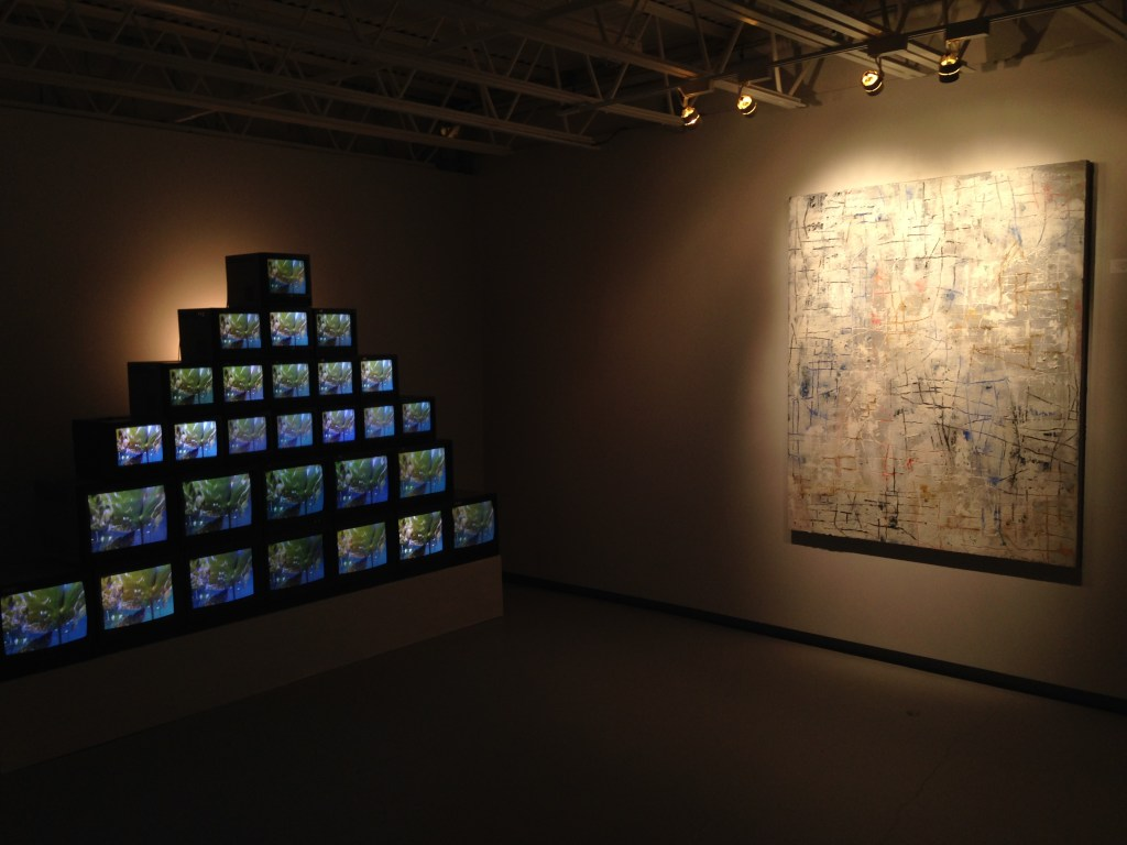 "Installation view of ""Pilgrim Pond Pyramid, 2013"" video by Madeleine Altmann and ""The Silver Morning, 2015"" painting by Joseph Caruso (courtesy of the artists and 555 Gallery, Boston)."