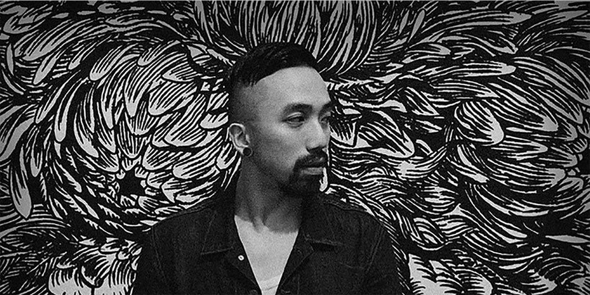 Artist Caratoes standing in front of one of his murals made while using Air Ink.