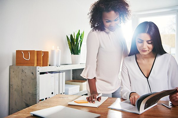 Businesswomen working on their branding on their office checking books to choose