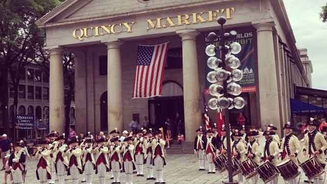 U.S. flag flies at Quincy Market in Boston (a 4th of July celebration is pictured) - WHDH Channel 7 image