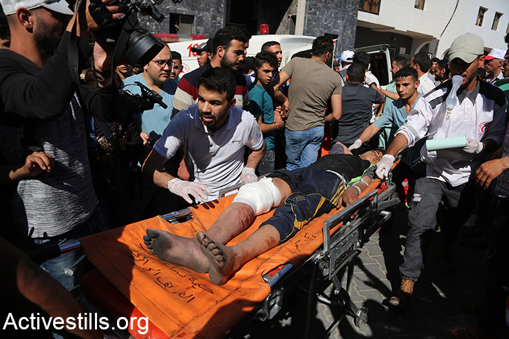 A wounded Palestinian is brought into al-Shifa hospital in Gaza City, after being shot by Israeli snipers during a protest on the Gaza-Israel border, May 14, 2018. (Mohammed Zaanoun/Activestills.org)