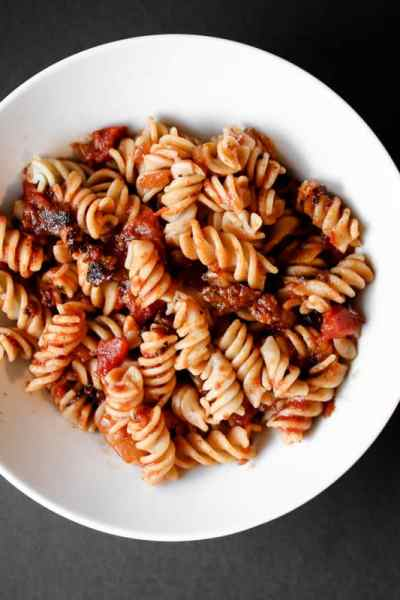 white bowl with pasta and Italian sausage red sauce