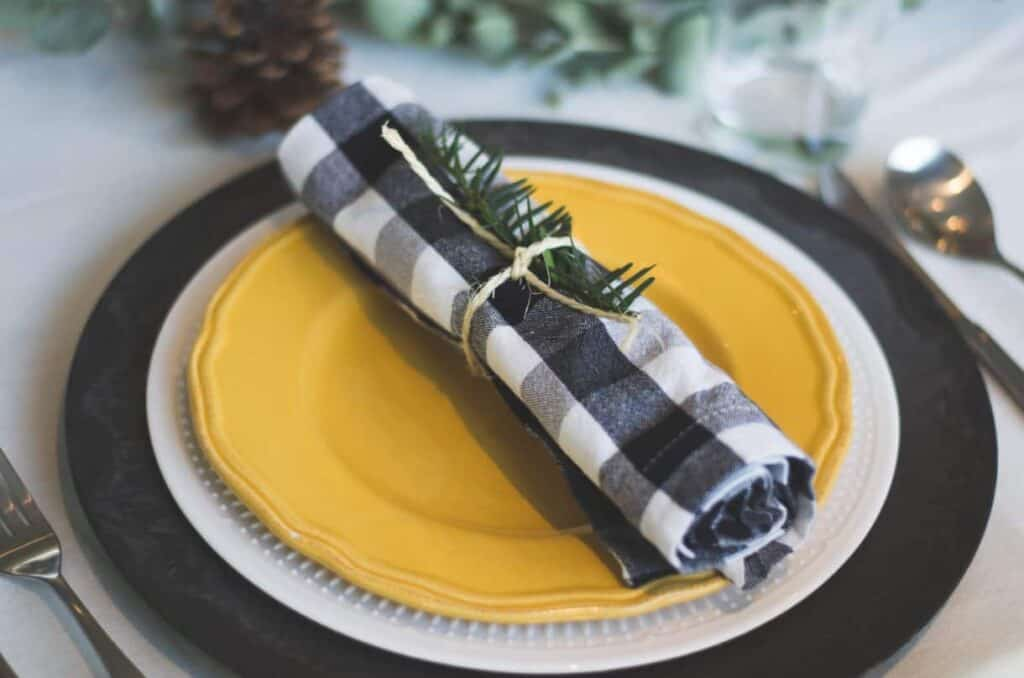 Photo by Libby Penner on Unsplash. Black and yellow holiday tablescape.