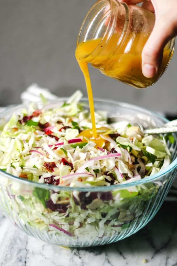 Apple Cider Vinaigrette pouring onto a big bowl of Cranberry almond thanksgiving slaw