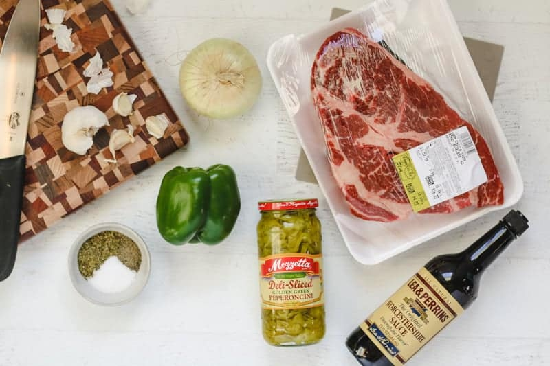 ingredients in Instant pot italian beef laid out, beef chuck, pepperoncini, bell pepper, onion, garlic, and spices