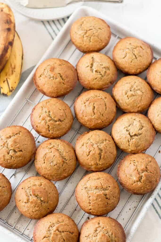 A dozen gluten free banana muffins on a wire rack, on a speckled baking sheet.