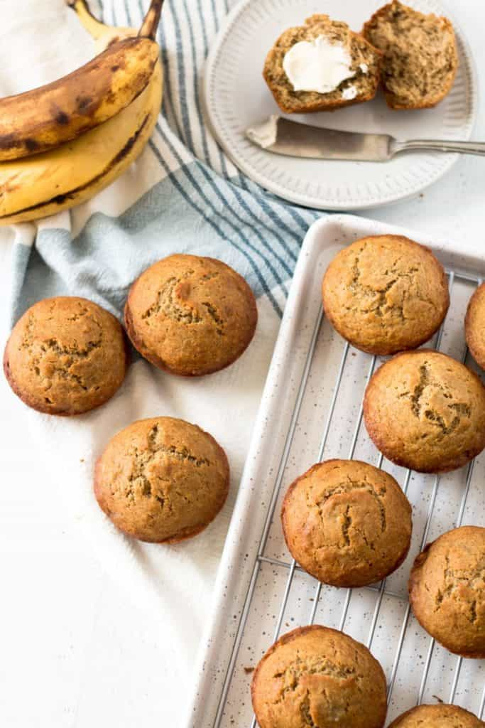 Gluten free banana muffins, one with butter, ripe bananas in background.
