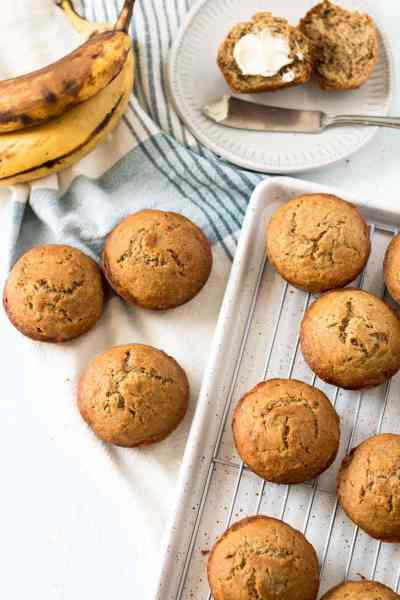 Gluten free banana muffins, one with butter, ripe bananas in background