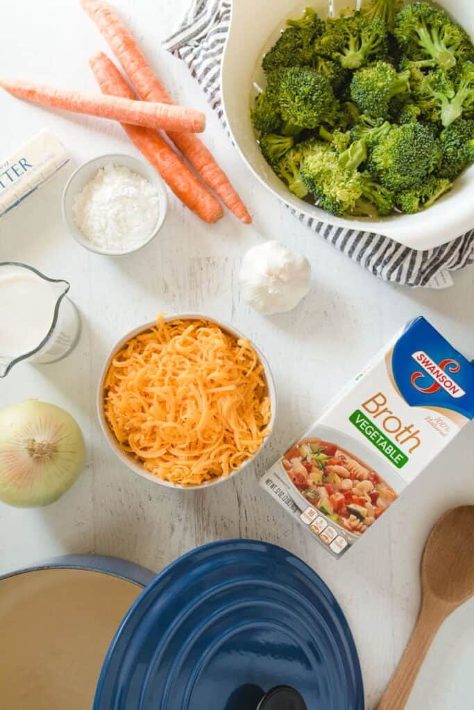 Ingredients laid out for broccoli cheddar soup: broccoli, cheddar cheese, garlic, onion, carrots, Swanson broth, butter, and brown rice flour.