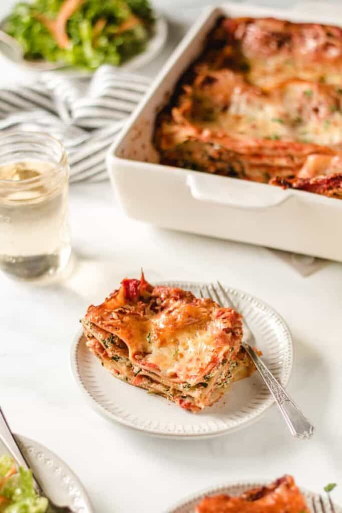 A slice of gluten free lasagna on a white plate.