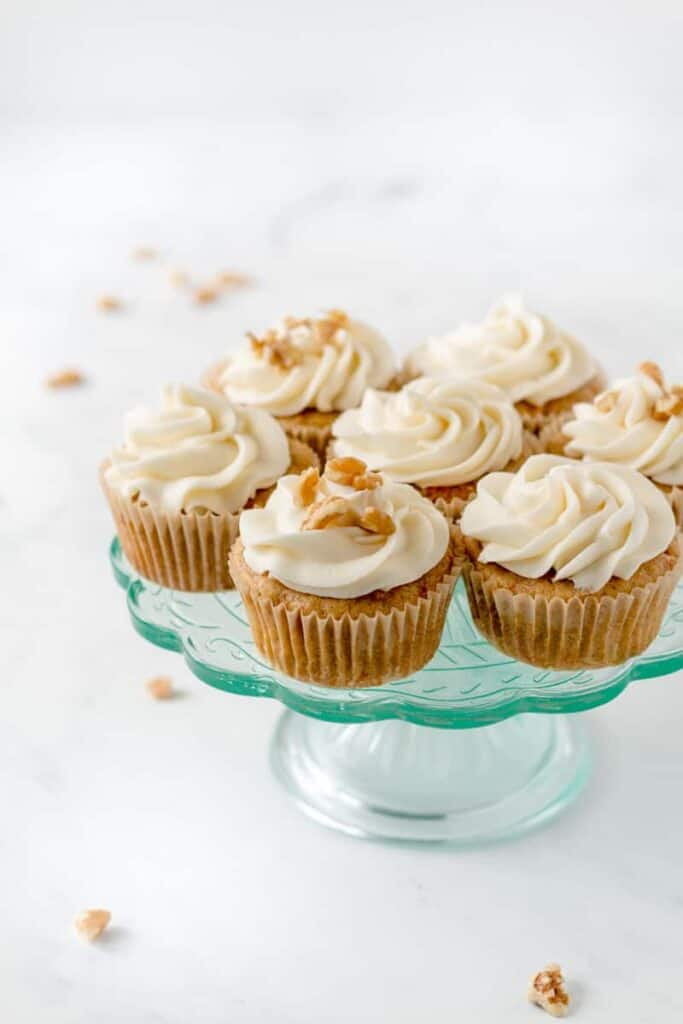 Carrot cake cupcakes with cream cheese frosting on an aqua cake stand.