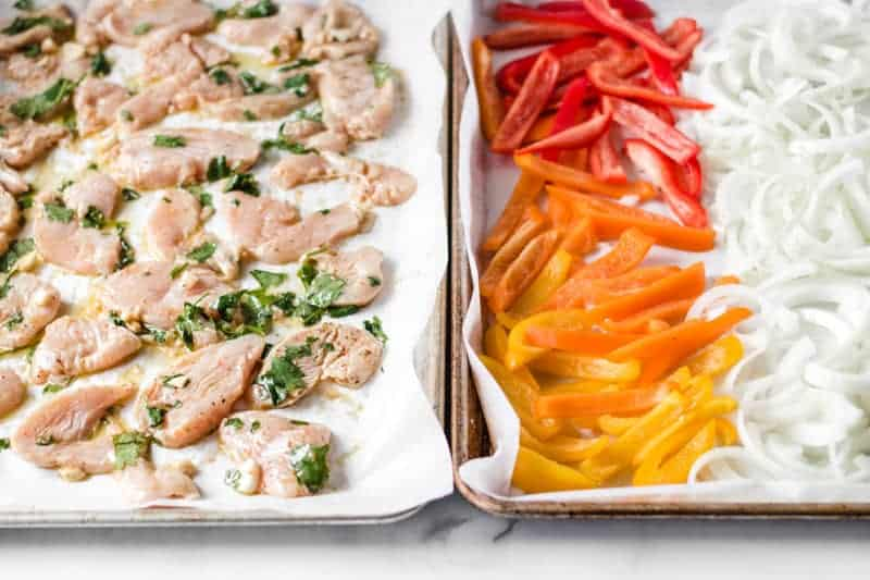 Chicken fajitas on two sheet pans, one with chicken, the other with bell peppers and onion.