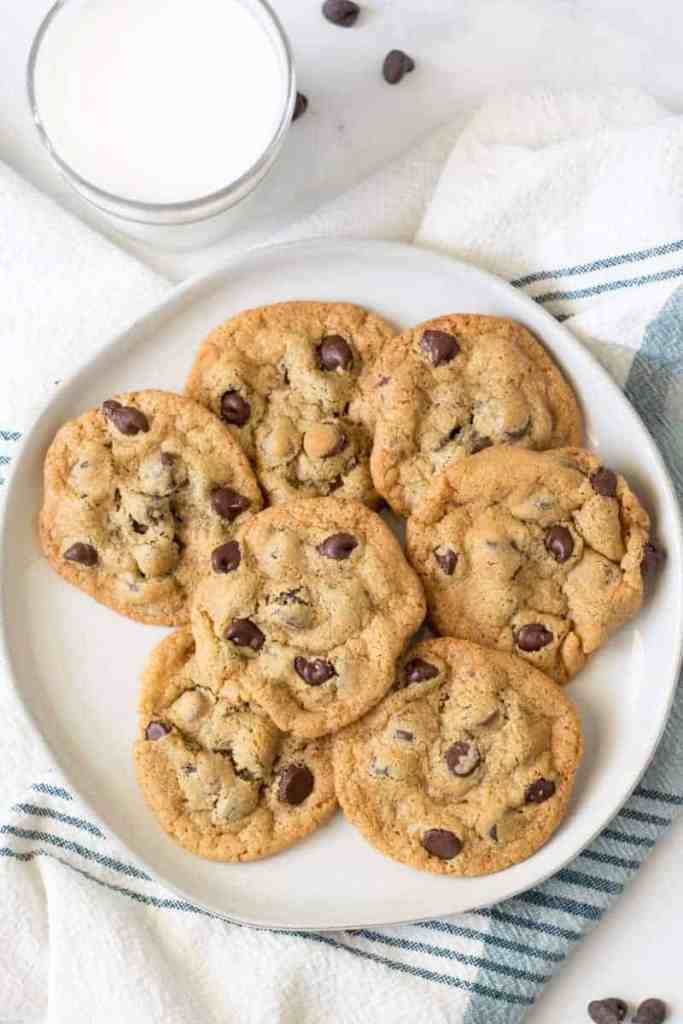 A plate full of chocolate chip cookies next to a glass of milk.