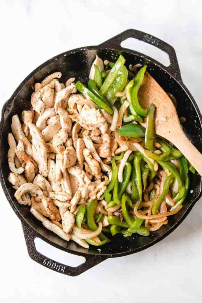 Lodge dual handle, cast-iron pan with sautéd chicken strips, onions, and bell pepper.