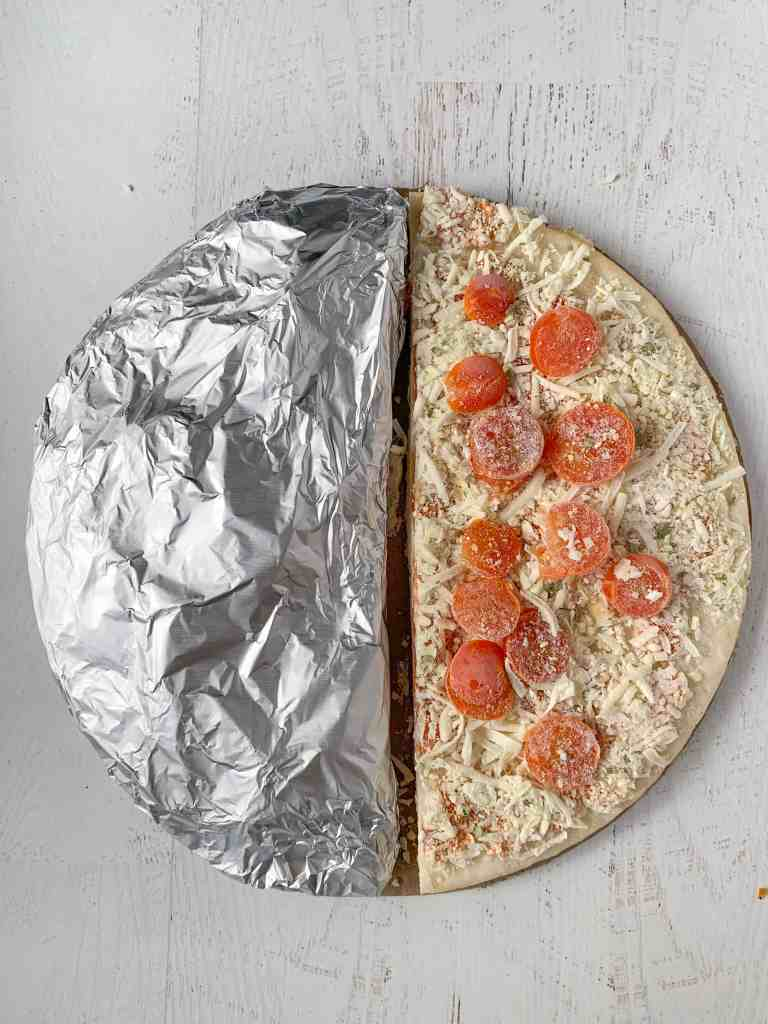 A frozen margarita pizza cut in half, half is wrapped in foil.