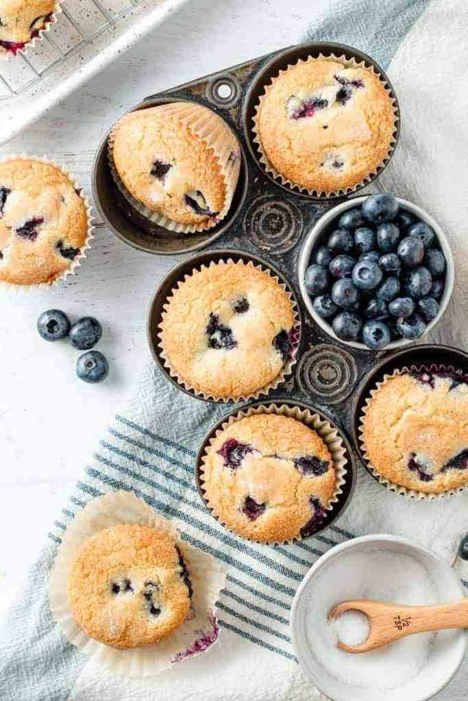 Gluten-free Blueberry Muffins and fresh blueberries fill a vintage muffin tin.