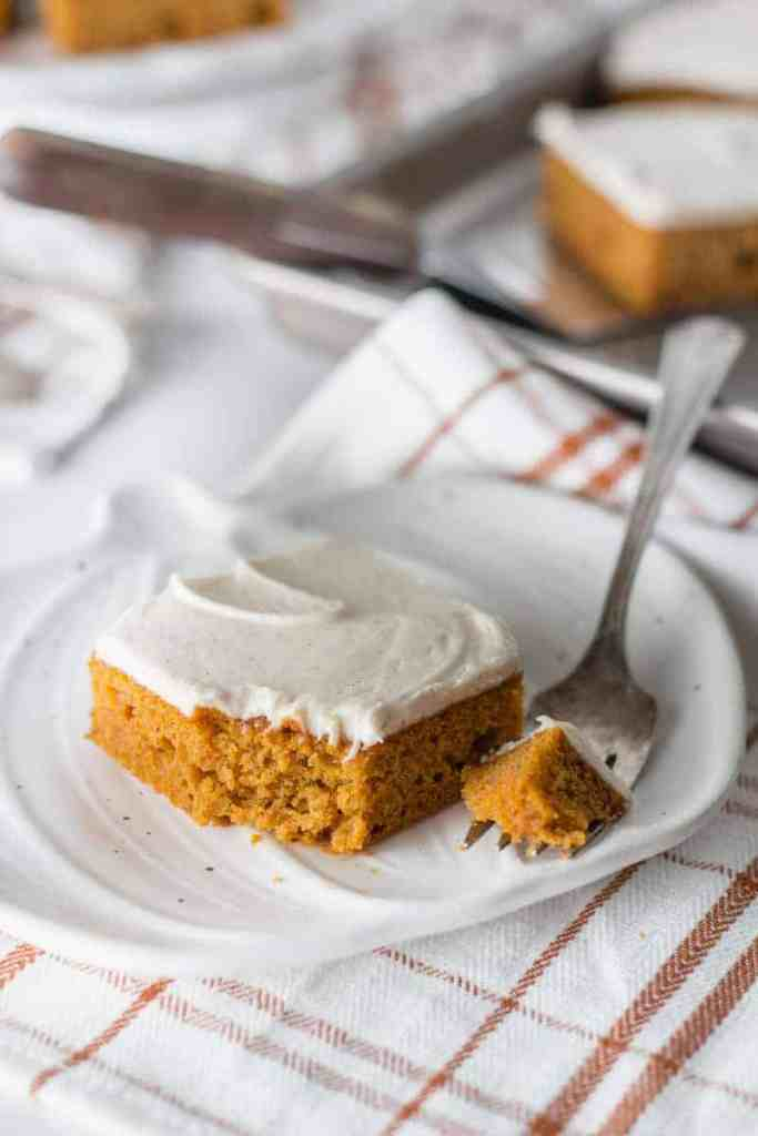 A slice of Gluten-free Pumpkin Bars on a white pumpkin plate. A bite removed, resting on a fork.