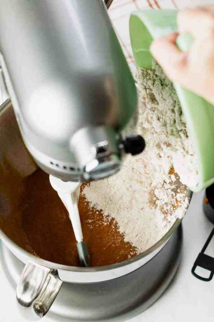 The dry ingredients are poured on top of the wet ingredients in the mixer.
